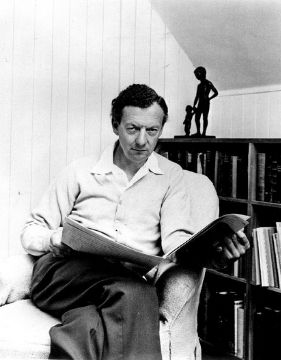 A photo of Benjamin Britten while he is reading a newspaper.